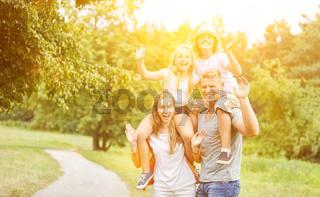 Familie und Kinder winken bei Ausflug im Sommer
