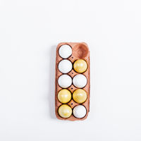 Tray of yellow Easter eggs on white background