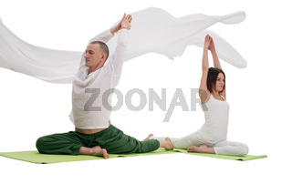 Man and woman doing yoga exercises in studio