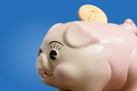 Single gold coin being placed in piggy bank