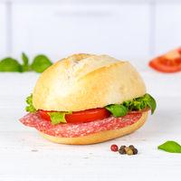 Brötchen Sandwich Baguette belegt mit Salami Schinken Quadrat auf Holzbrett