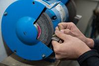 Facharbeiter schleift Metallstück mit Doppelschleifer - Nahaufnahme