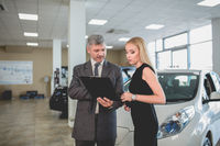 Vehicle dealer and young woman in auto showroom.