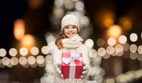 happy girl in winter clothes with gift box