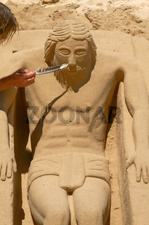 Young Man Working on Sand Sculpture of Jesus in Cadiz, Spain