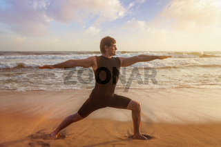 Man doing yoga asana Virabhadrasana 1 Warrior Pose on beach