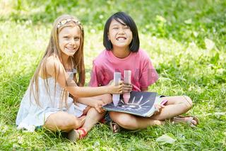 Asiatisches Mädchen malt mit Freundin ein Bild