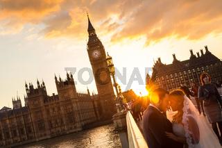Street scene of random people on Westminster Bridge in sunset, London, UK.