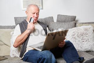 Senior überlegt beim online Shopping
