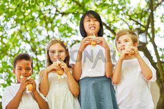 Multikulturelle Gruppe Kinder isst Baguette