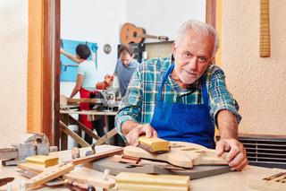 Alter Gitarrenbauer mit Schleifpapier