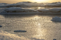 Strait between the islands covered by ice of Antarctica at sunset