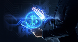 businessman with tablet pc and bitcoin hologram