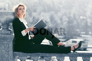 Young fashion business woman with a folder sitting on banister