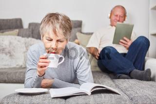 Ältere Frau trinkt Kaffee und liest entspannt