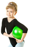 A girl playing with a green ball