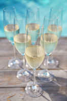 Champagne glasses on wooden background near pool