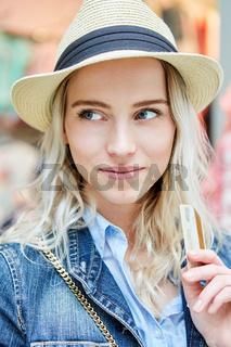 Junge blonde Frau überlegt beim Einkaufen