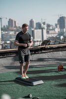 Young athletic man getting ready for workout on the roof.