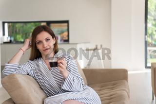 young woman in a bathrobe enjoying morning coffee