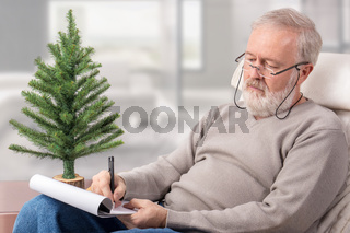 Grandfather making the shopping list for winter holidays