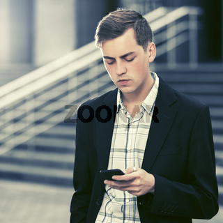 Young handsome business man using smart phone walking in city street