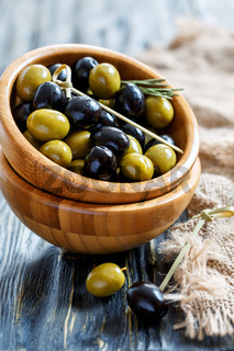 Bowls with black and green olives and bamboo skewers.