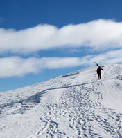 Skier with skis go up to top of snowy mountain