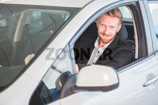Happy man buying new car in auto showroom.