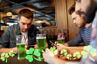 friends with smarphones and green beer at pub