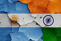 flags of Argentina and India painted on cracked wall