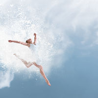 Beautiful ballet dancer jumping with cloud of powder