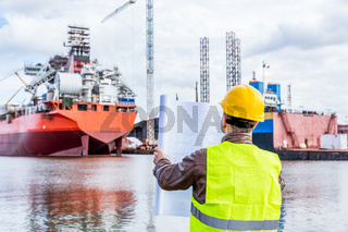 Shipbuilding engineer checking documents at the dock side in a port.
