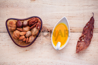 Selection food sources of omega 3 and unsaturated fats. Super food high vitamin e and dietary fiber for healthy food. Almond ,pecan ,olive oil ,hazelnuts and walnuts on wooden background flat lay.