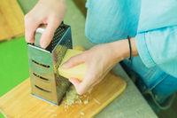 Close-up of a woman's hands rub the parmesan cheese on a metal grater.