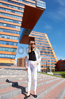 Modern young woman on the steps of Building of Information Technology Center in Akademgorodok. The symbol of Novosibirsk technopark