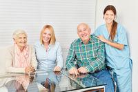 Glückliche Familie mit Senioren Paar und Pflegerin
