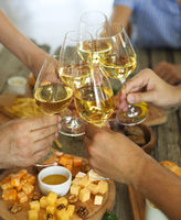 Hands with white wine toasting over served table with food