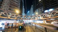 Illuminated street of Hong Kong with rails and pedestrian bridge
