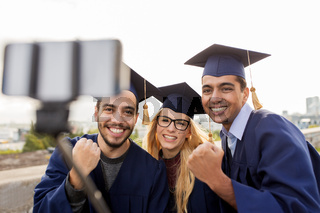 happy students or graduates taking selfie outdoors