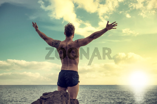 Muscular man on the beach in front of rising sun