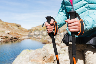 Close-up of female hands with trekking sticks for Nordic walking against the background of alpine lake and distant Caucasian Rocks