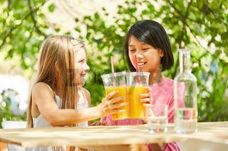 Zwei Mädchen stoßen mit Orangensaft an