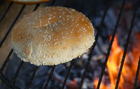 Close up sesame bun for burger on bbq fire grill