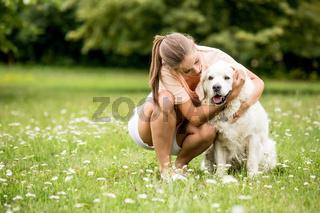 Frau kuschelt mit ihrem Retriever