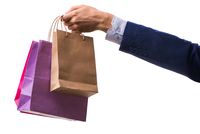 Hand holding shopping bags with christmas shopping on white back