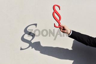 Hand hält einen Paragraphen mit Silhouette