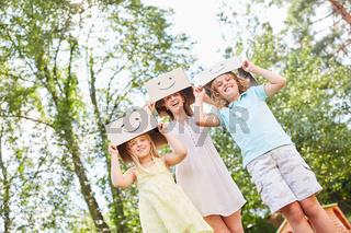 Kinder mit lustig bemalten Pappkartons