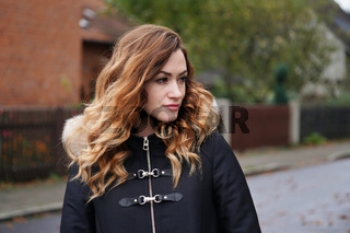 thoughtful young woman wearing winter coat on suburban street