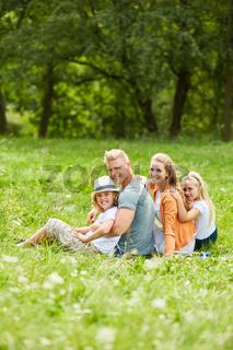 Glückliche Familie sitzt im Garten